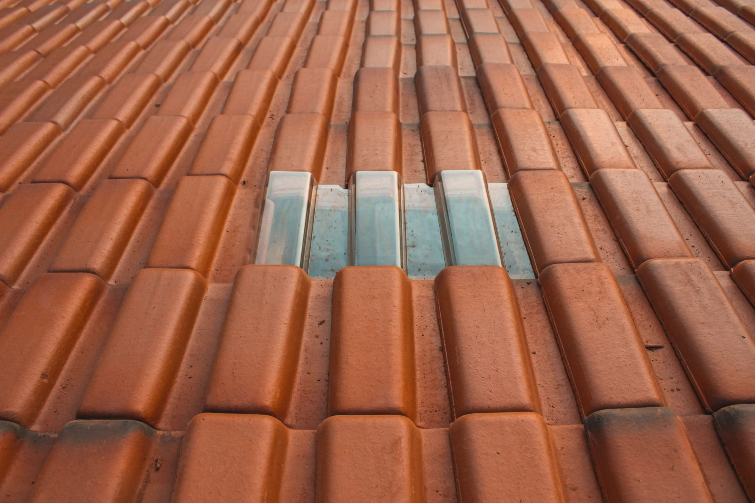How to Choose the Right Roofing Contractor - A close up shot of rust-colored roofing material with a silver-colored rectangle in the center.